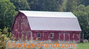 Horse shed, barn made of wood and painted red.